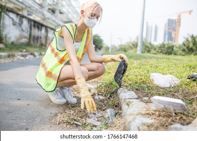 Community service - Young female volunteer person cleaning the littered streets in a urban environment by picking up trash laying on the ground while wearing a face mask and a reflective vest.