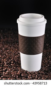 A commuter coffee cup rests on roasted coffee beans. 24MP camera.