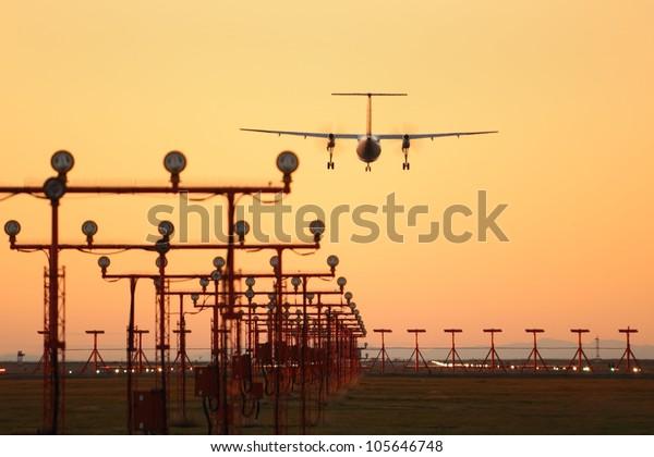 Commuter Plane Landing, Sunset. A commuter plane landing at sunset at Vancouver International Airport, YVR. Richmond, British Columbia, Canada.