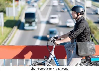 Commuter riding e-bike, crossing overpass
