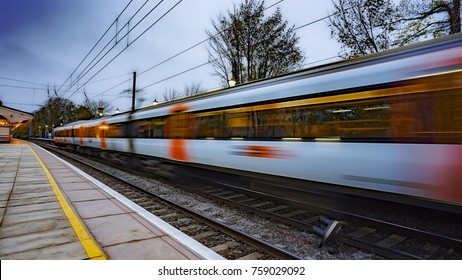 Commuter train departing a UK station and gathering speed