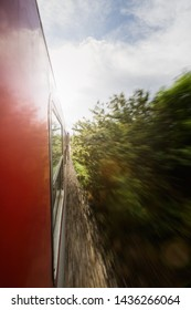 A commuter train traveling at speed past motion blurred countryside vegetation.