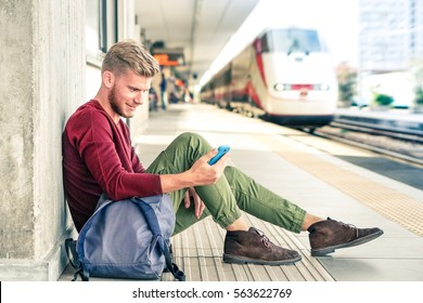 Commuter traveler man looking down at phone waiting train in railway station - Handsome caucasian guy sitting on platform using mobile with locomotive background - Soft desaturated vintage filter