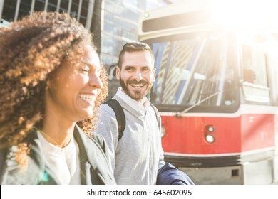 Commuters in the city walking and smiling with a tram on background. Modern business man and woman wearing smart casual clothes in the city. Urban lifestyle