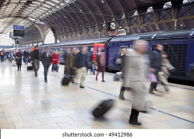 Commuters at Paddington station blurred with slow shutter speed, with all logos removed and all faces blurred beyond recognition.