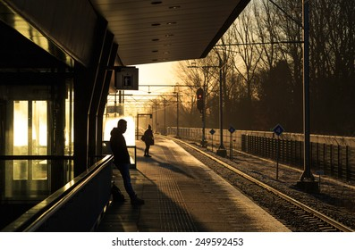 Commuters waiting for a train on a winter morning at the train station.