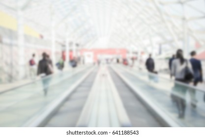 Commuters walk. Background with an intentional blur effect applied. Humans and location not recognizable.
