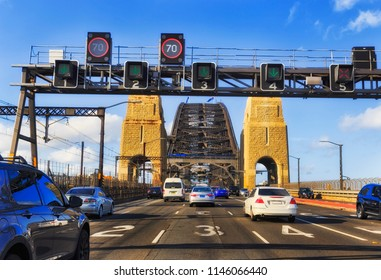 Commuting motor traffic entering Sydney Harbour bridge escaping from the city after business day on multi lane Warringah freeway heading north through steel archs.