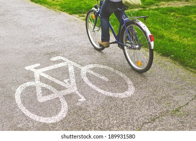 Commuting to work on a bicycle. Woman riding bicycle on a bike path marked with symbol.