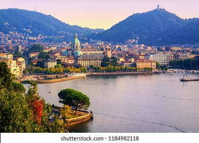 Como city historical town center and Alps mountains on Lake Como, Italy, in warm sunset light