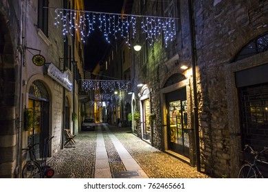 COMO, ITALY - DECEMBER 2, 2016: Night view of Via Vitani street in Como Old Town, Lombardy, Italy. Como is the 4th most visited city in Lombardy after Milan, Bergamo and Brescia