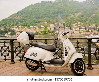 Como/Italy - April 20, 2014: A white Vespa is parked beside Lake Como. Vespa is an Italian brand of scooter manufactured by Piaggio. The name means wasp in Italian.