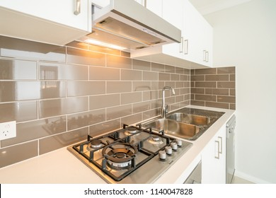 Compact Australian house kitchen with cooktop, stove, sink, dish