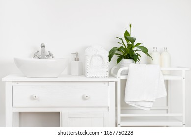Compact bathroom interior with white vintage furniture, shelf, towels and sink