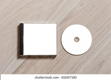 Compact disc template with plastic box with white isolated blank for branding design. CD jewel case mock up with clean free space with booklet for print on wooden table. Top view
