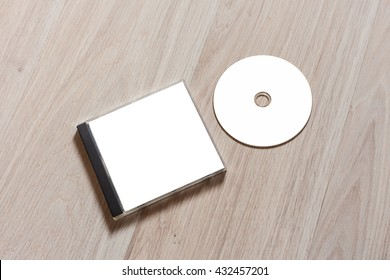 Compact disc template with plastic box with white isolated blank for branding design. CD jewel case mock up with clean free space with booklet for print on wooden table. Perspective view