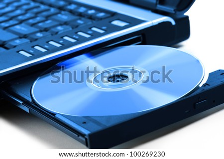 compact disk inserted on notebook drive, on white background