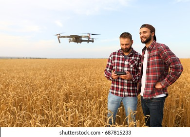 Compact drone hovers in front of two hipster men. Quad copter flies near pilot. Farmer and agronomist exploring harvest vith innovative technology taking aerial photos and videos from above