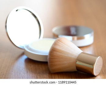 compact face powder and makeup kabuki brush on wooden background close up