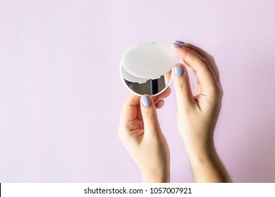 A compact, compact mirror in women's hands. On a lilac bright background. Makeup female accessories