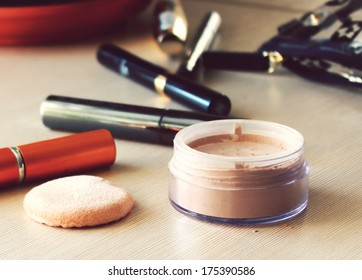 Compact pocket powder and a powder puff and other cosmetics on the table