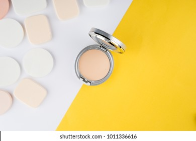 Compact powder and sponges on a white and yellow background