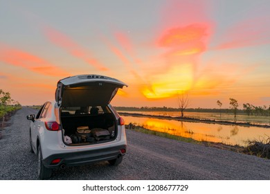 compact SUV car with sport and modern design parked on concrete road by the sea at sunset. Environmentally friendly technology. Business success concept