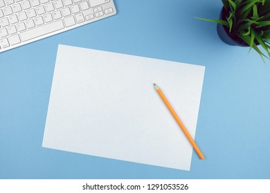 Compact white wireless keyboard on a blue backgroundwith a plant and sheet of white paper, orange pencil. Copy space.