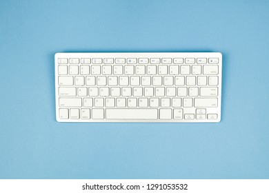 Compact white wireless keyboard on a blue background.