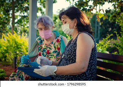 Companion or volunteer teaches an elderly woman how to use a computer tablet. Both in protective face masks sitting on a park bench. Summer sunny day.
