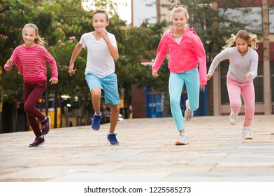 Company of active kids are jogning together in the park.