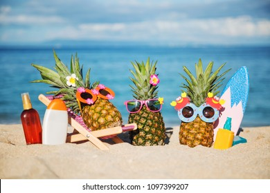 Company of attractive pineapples in cheerful sunglasses resting on the sand beach of tropical island. Surfing. Wearing funny sunglass. Tropical vacation concept. Sunbathing using sunscreen lotion