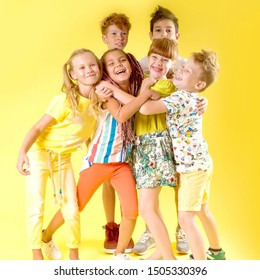 The company of beautiful cheerful children are having fun on a yellow background. Fashion kids, baby hairstyles