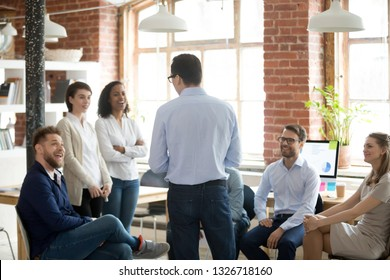 Company boss executive manager talking with company members during briefing at coworking modern comfortable office. Multiracial diverse businesspeople listening business coach during workshop seminar