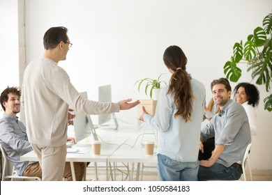 Company boss introducing new employee to colleagues, executive and friendly team welcoming greeting hired woman newcomer member holding box with belongings on first day at work in office, rear view