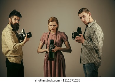Company of busy photographers. Vintage photography concept. Men in checkered clothes, retro style. old cameras, filming, working. Men and woman on strict faces on grey background.