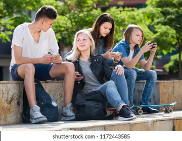 Company of carefree teenagers sitting and looking at their mobile phones in park
