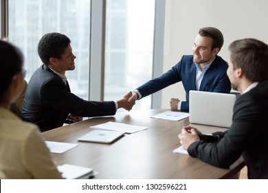 Company ceo handshaking african employee at corporate group meeting promoting or welcoming, satisfied caucasian boss and black employee shake hands, acknowledgement recognition gratitude concept