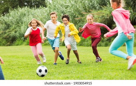 Company of children playing football on the playground in park