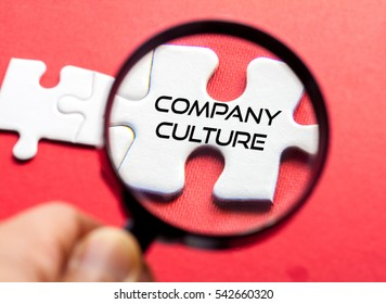 Company Culture written on white puzzle with magnifier glass,conceptual