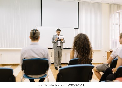Company director on a presentation with workers on a conference room background. Business international convention. Copy space.