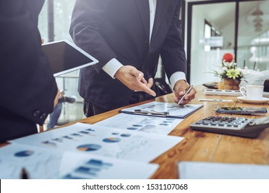 Company employees using tablet with business chart meeting room colleagues financial charts.