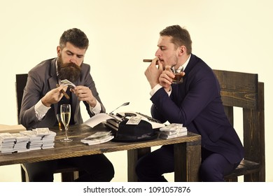 Company engaged in illegal business. Men sitting at table with piles of money and typewriter. Illegal business concept. Businessmen discussing illegal deal while drinking and smoking, white background