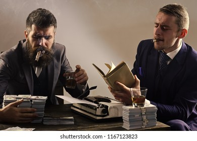 Company engaged in illegal business. Men sitting at table with piles of money and typewriter. Illegal business concept. Businessmen discussing illegal deal while drinking and smoking, grey background.