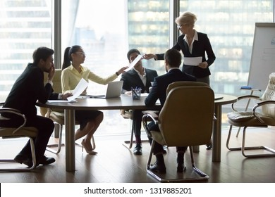 Company executive leader giving papers presenting new business plan to diverse employees team at group meeting, ceo manager handing report to workers discuss corporate paperwork in modern office