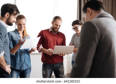 Company of five people actively discussing new project