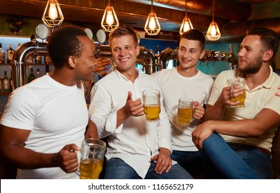 Company of four cheerful men wearing in white top and jeans, enjoying light beer in stylish pub, sitting at bar counter. Friends communicate, laughing and having fun together. Concept of friendship.