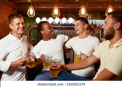 Company of four handsome men wearing in white top and jeans, holding glass of beer, smiling and embracing. Positive friends communicate, laughing and having fun together. Concept of man friendship.