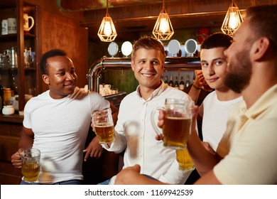 Company of four handsome men wearing in white top and jeans, listening carefully story of one of men, all looking at him. Friends communicate, having fun together, enjoying light beer in stylish pub.