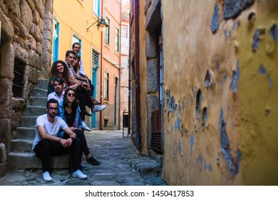 Company frends of young people sitting on a narrow street of old European city.